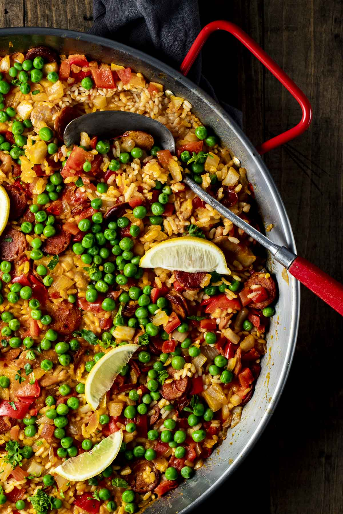 Overhead view of paella topped with lemon slices and peas.