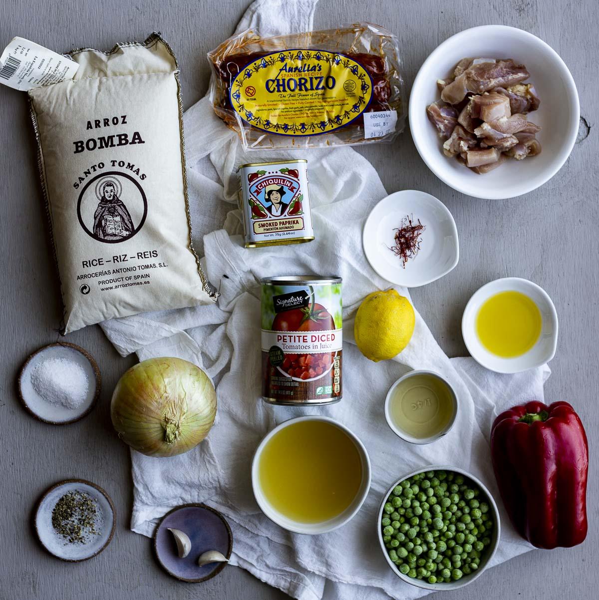 Ingredients to make Spanish chicken and chorizo paella arranged individually.