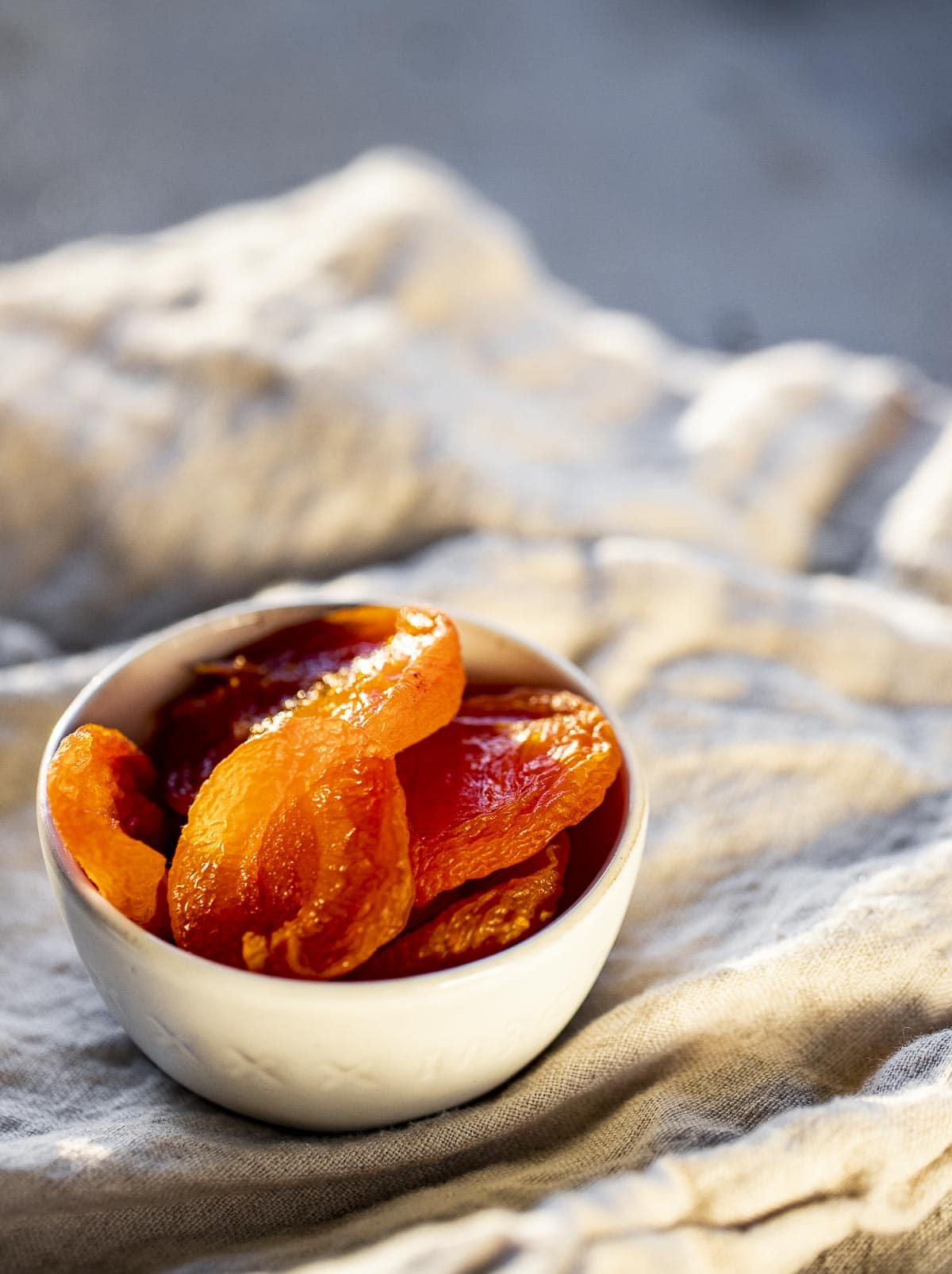 Dried apricots in a white dish on a white cloth.