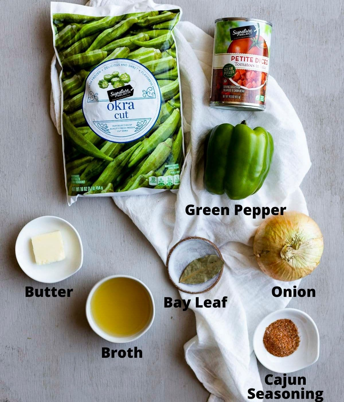 Ingredients to make smothered okra arranged individually and labelled.