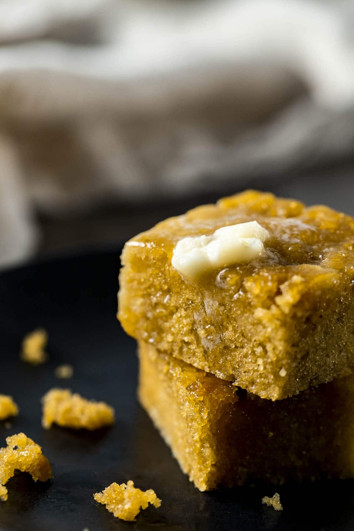 Two square pieces of cornbread with butter on top.