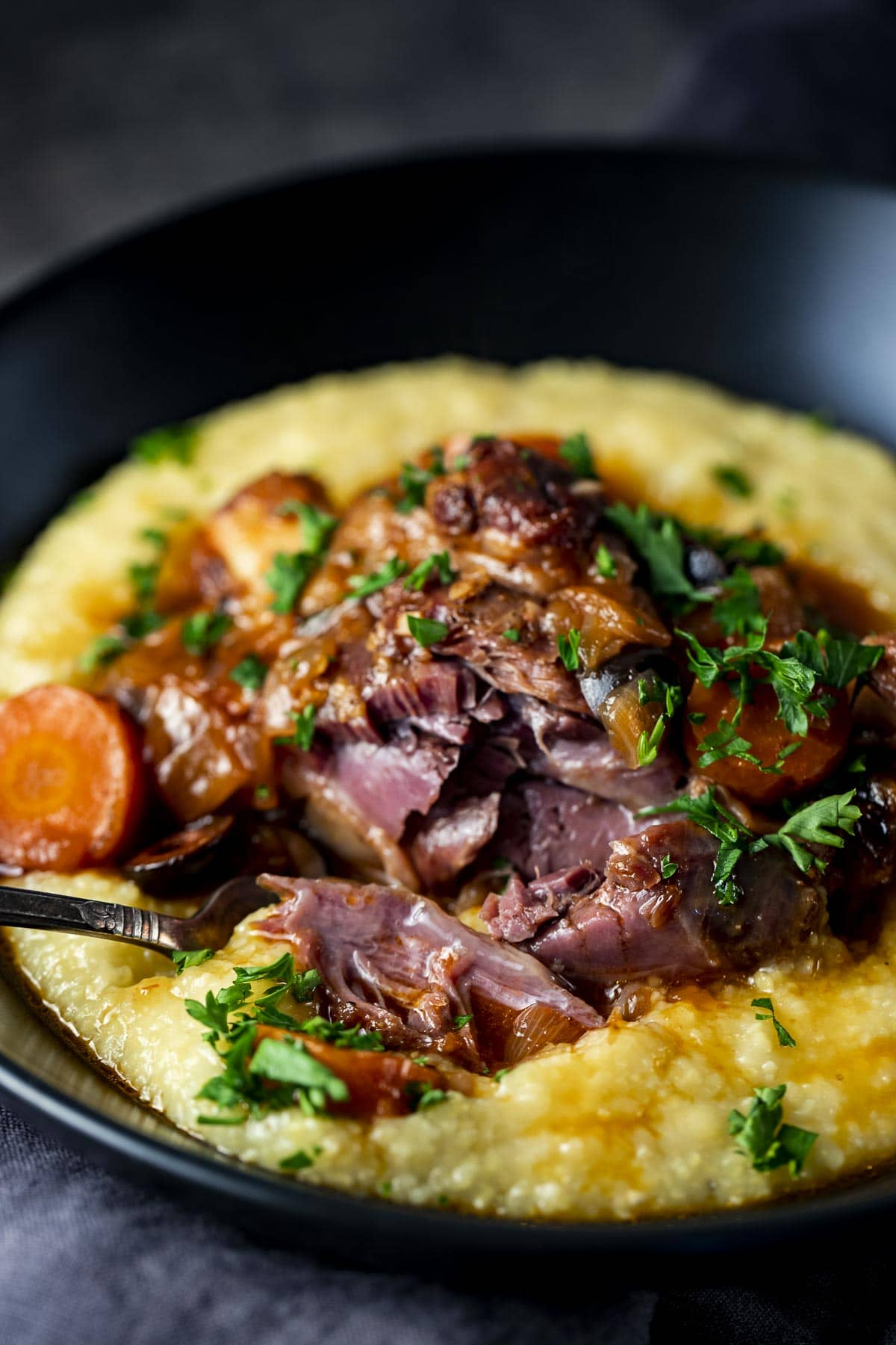 Lamb shank served in a bowl on top of creamy polenta.