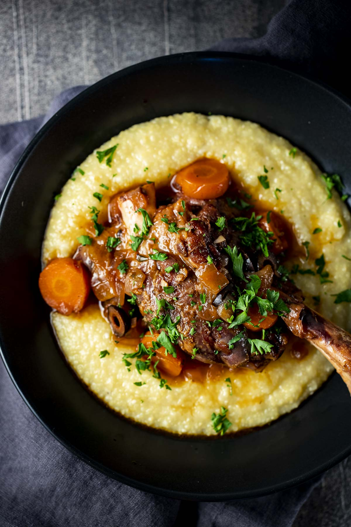 Overhead view of lamb shanks served on top of polenta in a bowl.