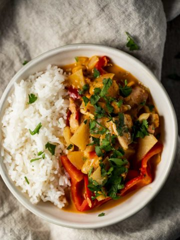 Pineapple chicken curry in a bowl with rice.