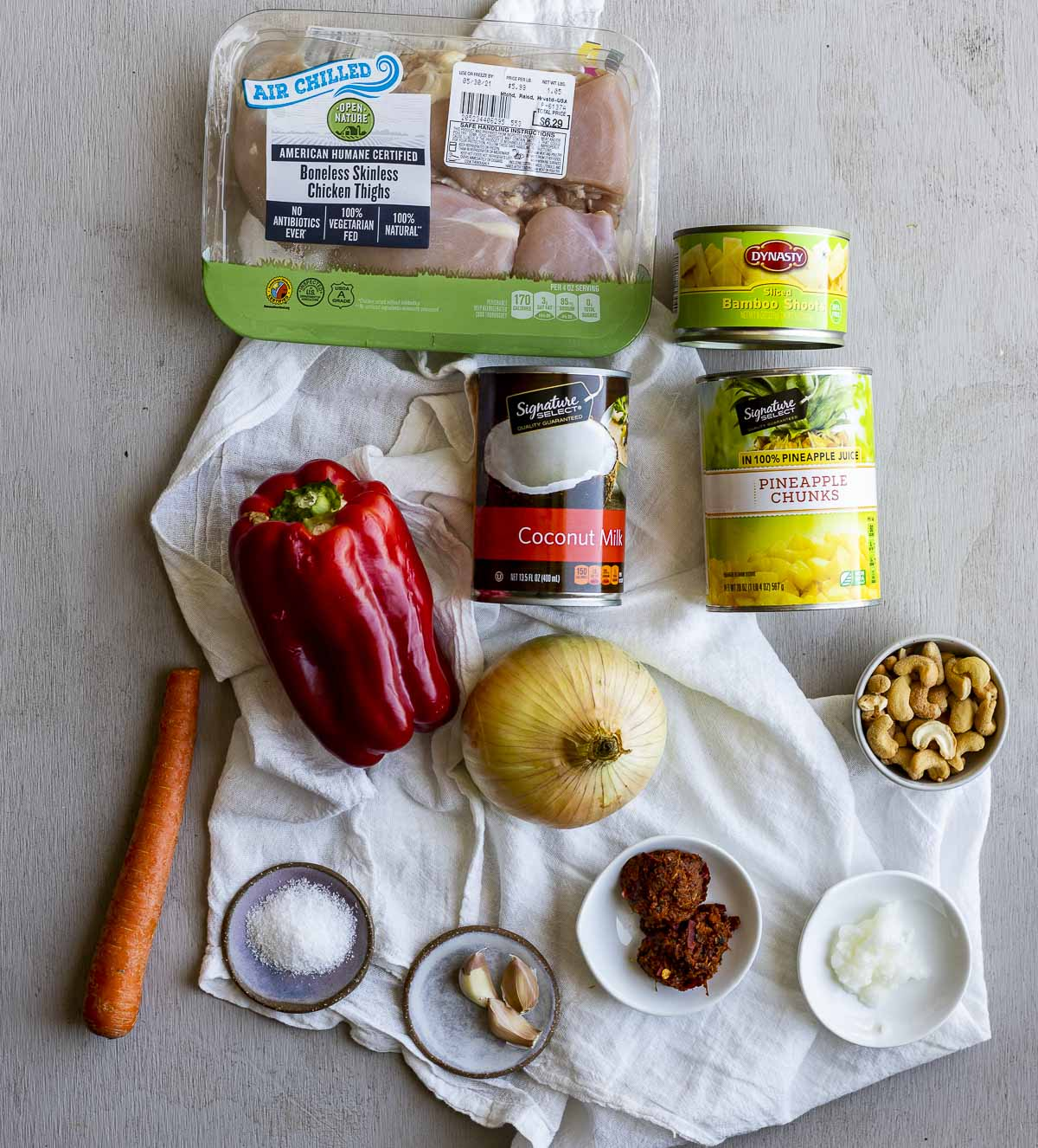 Ingredients to make pineapple chicken curry arranged individually on a white cloth.