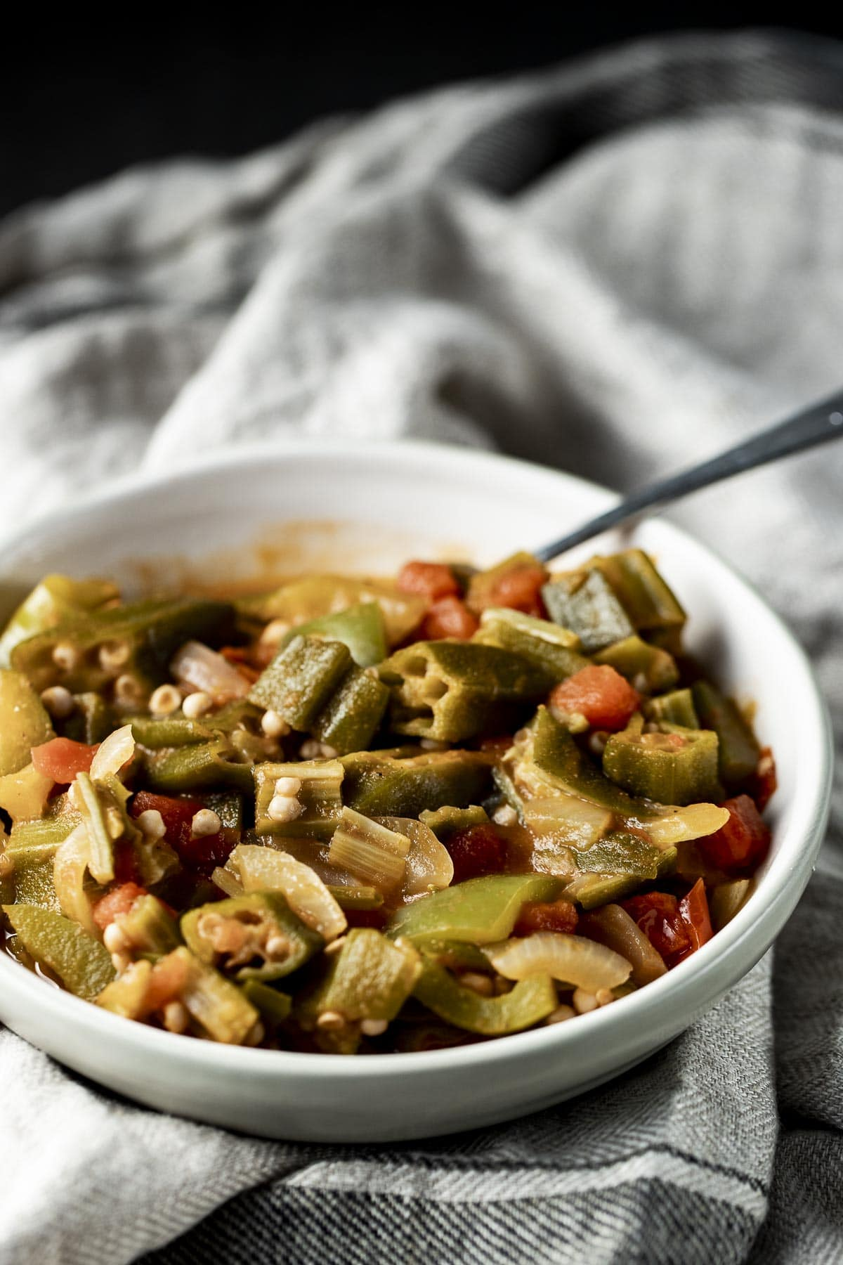 Smothered okra in a bowl with a spoon inserted into it.