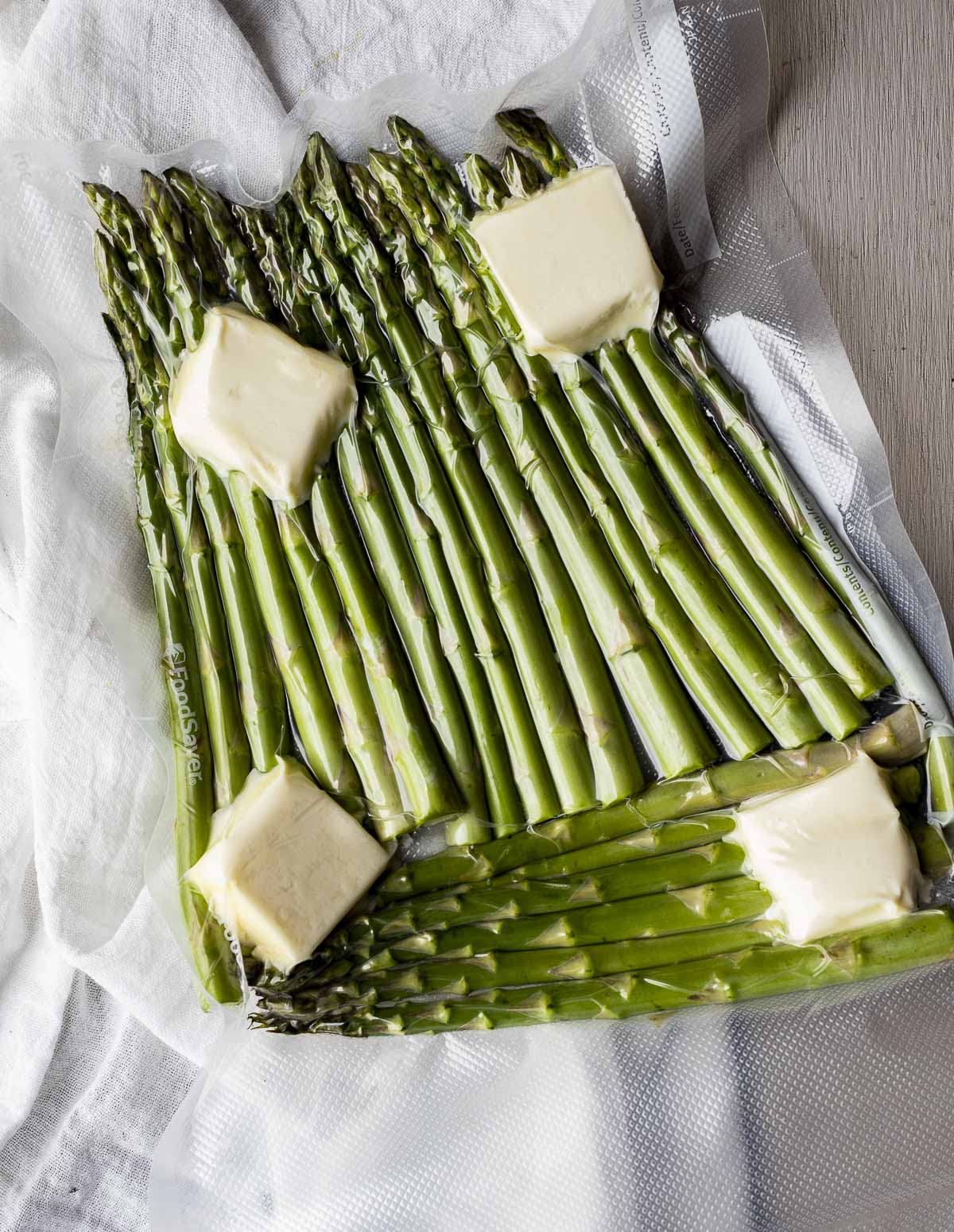Asparagus spears and butter vacuum sealed in a bag.