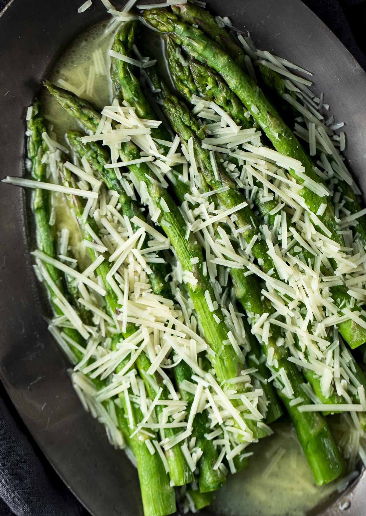 Sous vide asparagus in melted butter and topped with cheese.