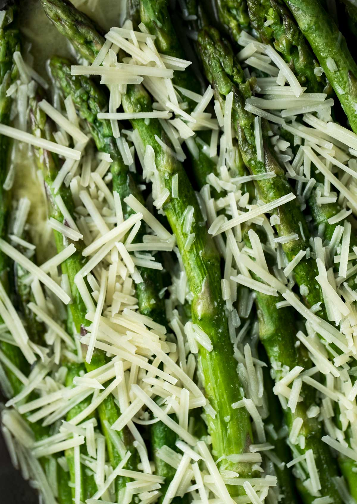 Overhead view of butter poached asparagus topped with parmesan.