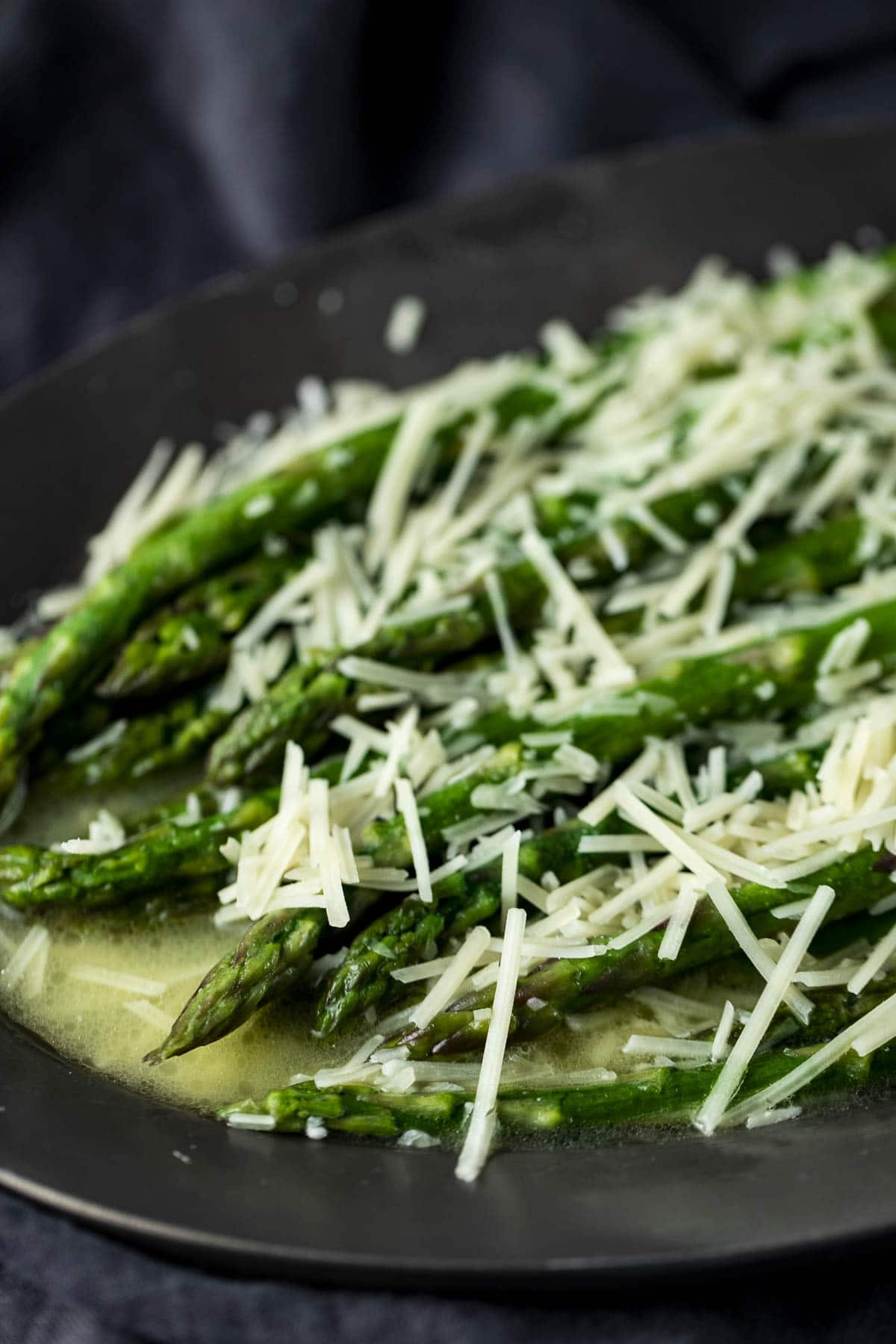 Side view of butter poached asparagus topped with grated parmesan.