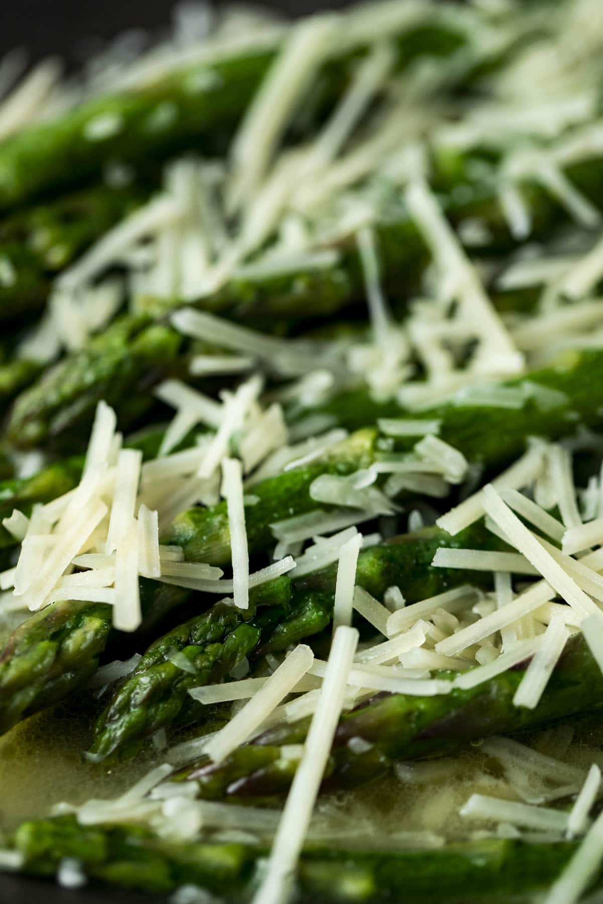 Up close view of sous vide asparagus topped with grated parmesan cheese.