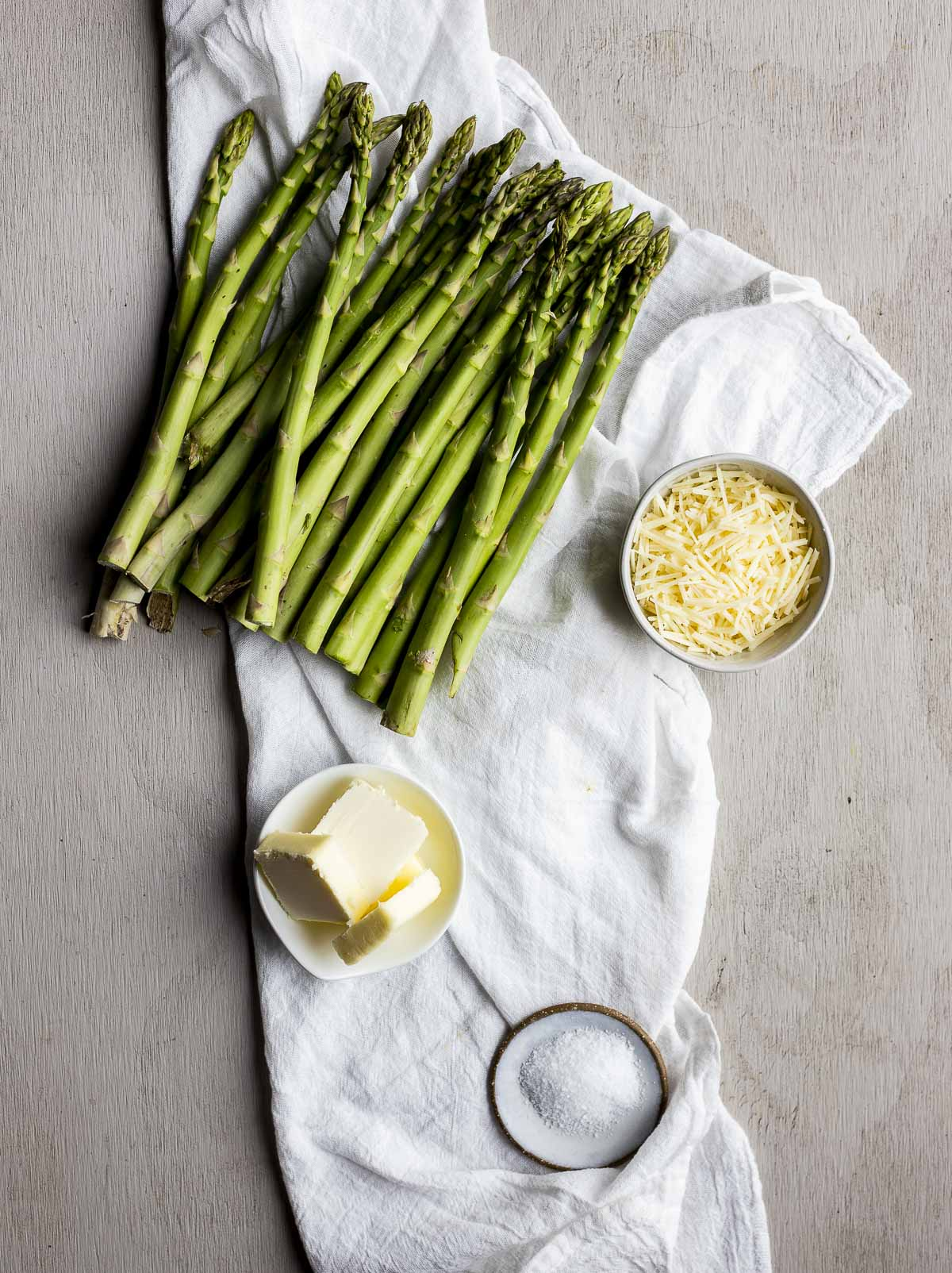 Ingredients to make sous vide asparagus arranged individually on a white cloth.