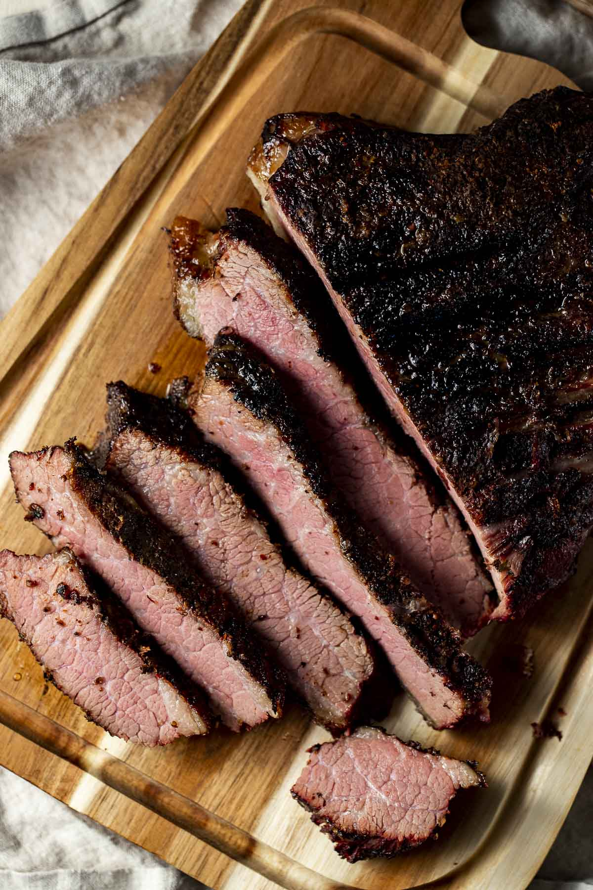 Overhead view of slices of brisket on a wooden board.
