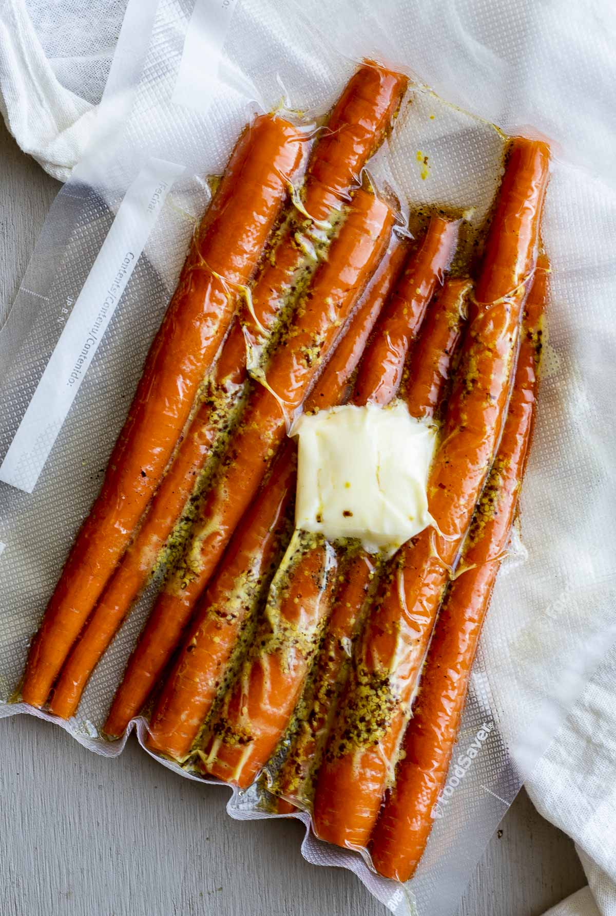 Raw whole carrots vacuum sealed with butter and other ingredients.