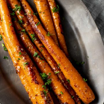 Overhead view of sous vide whole carrots with glaze on a serving tray.
