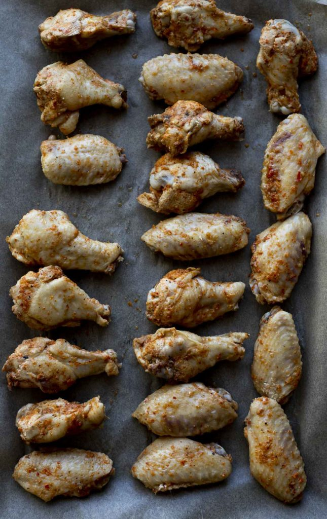 cooked chicken wings on a baking sheet