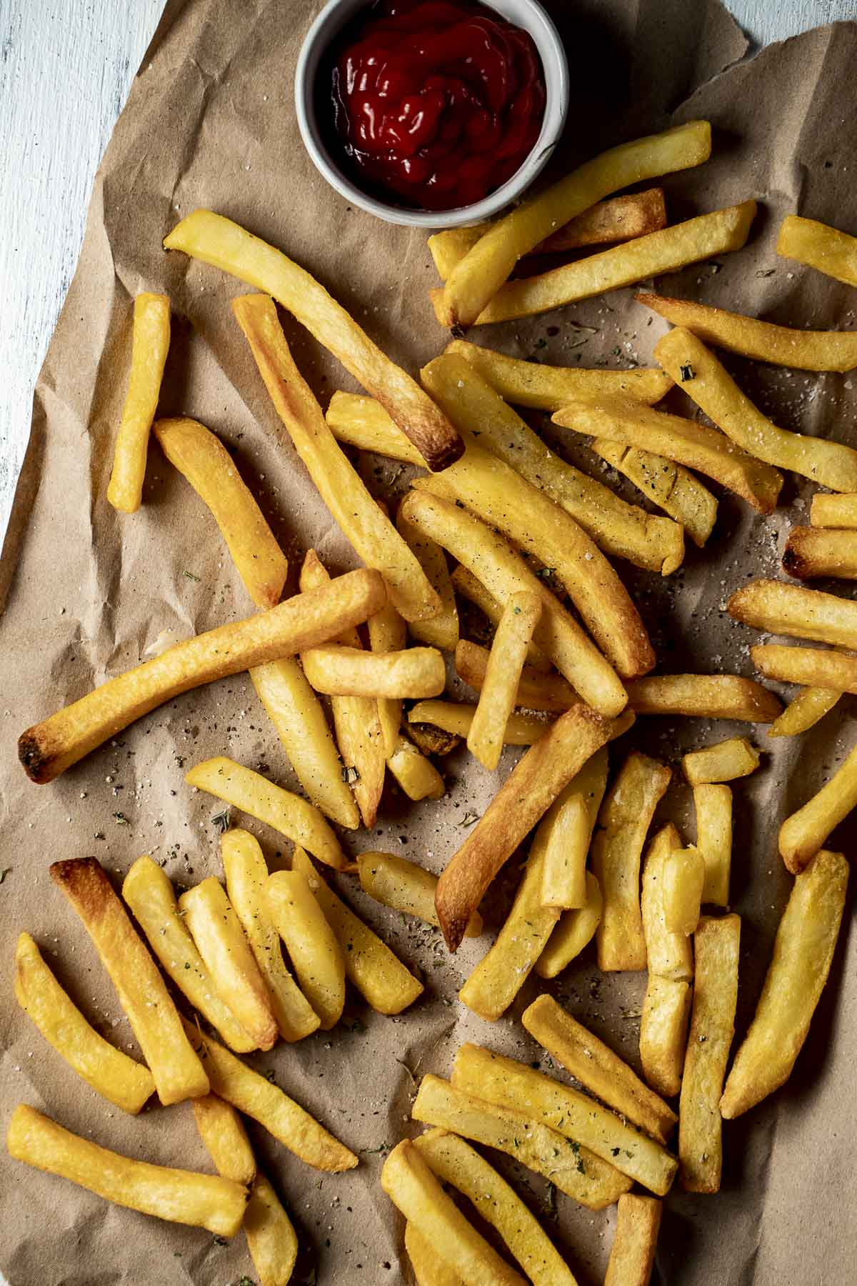 Golden brown french fries arranged on a sheet of brown paper with ketchup on the side.