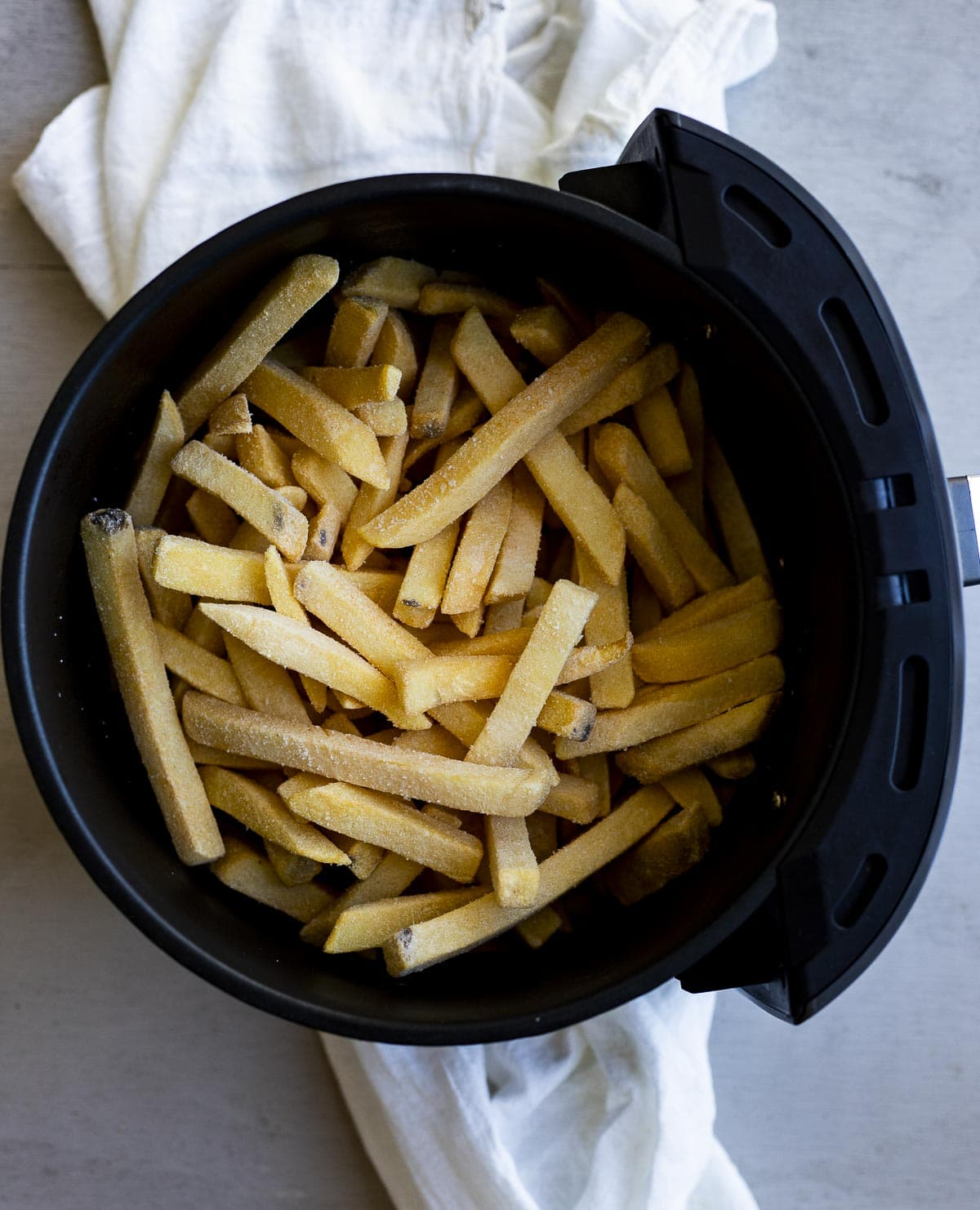 Overhead of frozen french fries in an air fryer basket.
