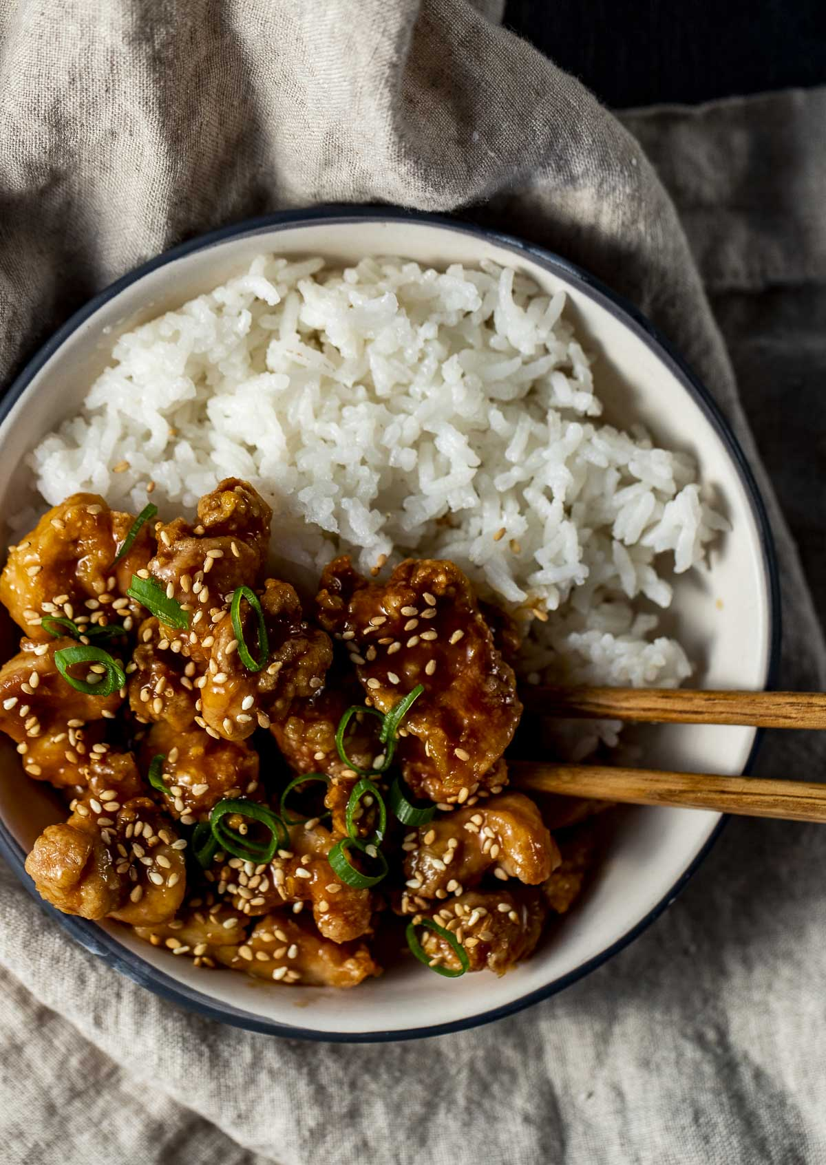 Overhead view of orange chicken and rice in a bowl with chop sticks.