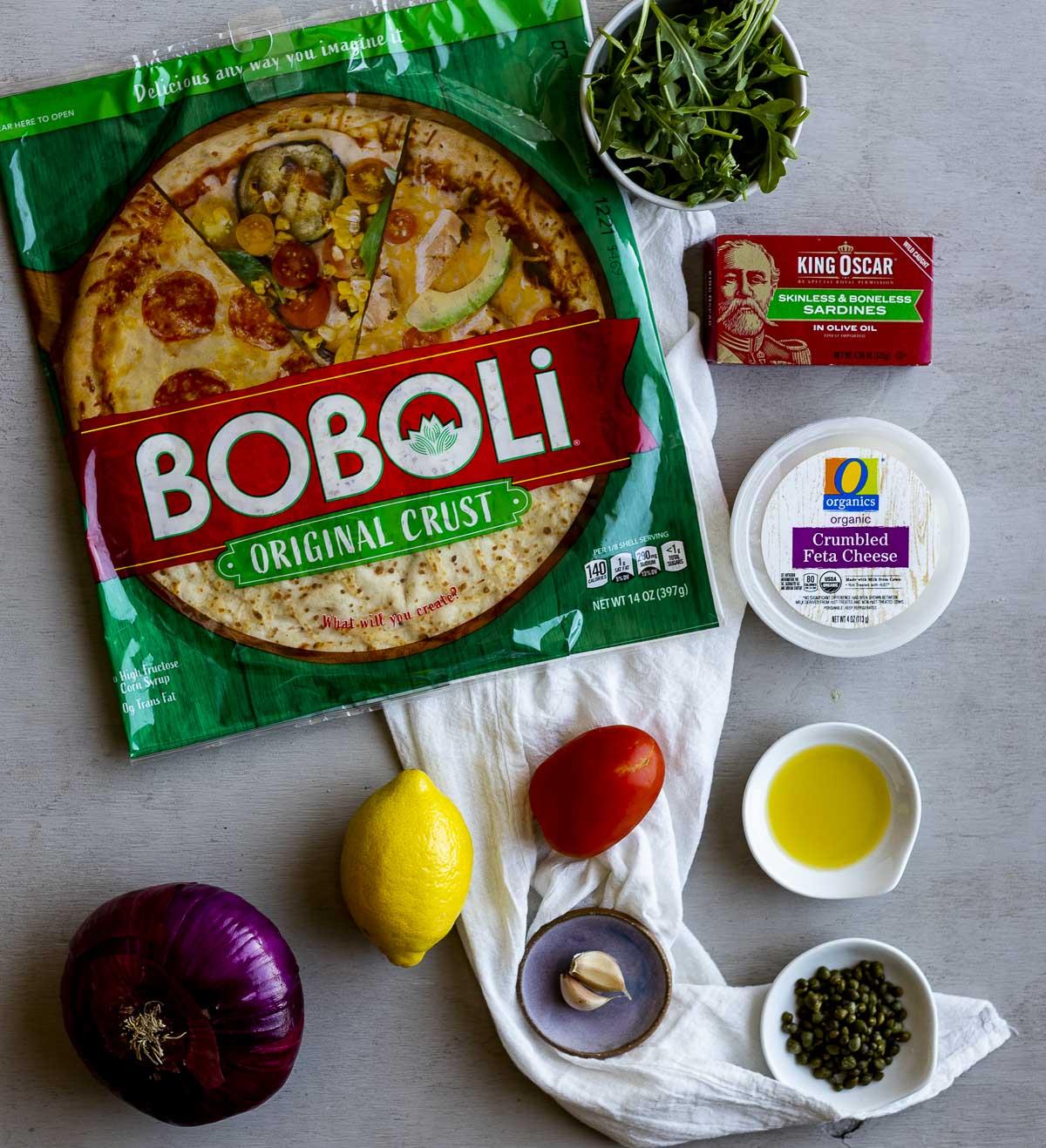 Ingredients to make sardine pizza arranged individually.
