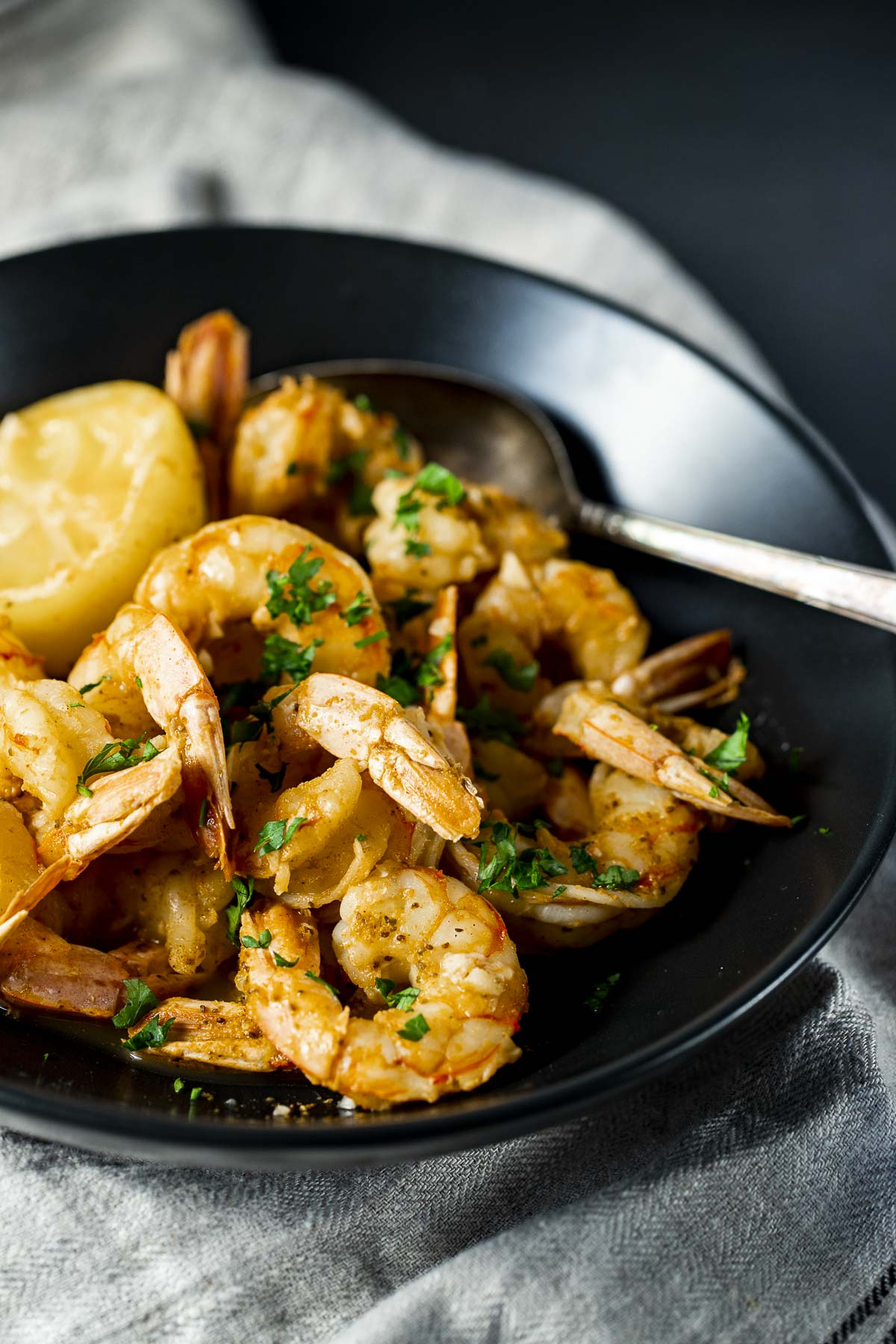 Instant Pot shrimp in a black bowl with a spoon.