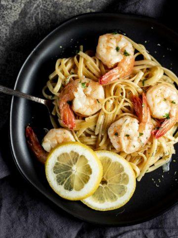Instant Pot shrimp scampi served on a black plate with lemon slices.