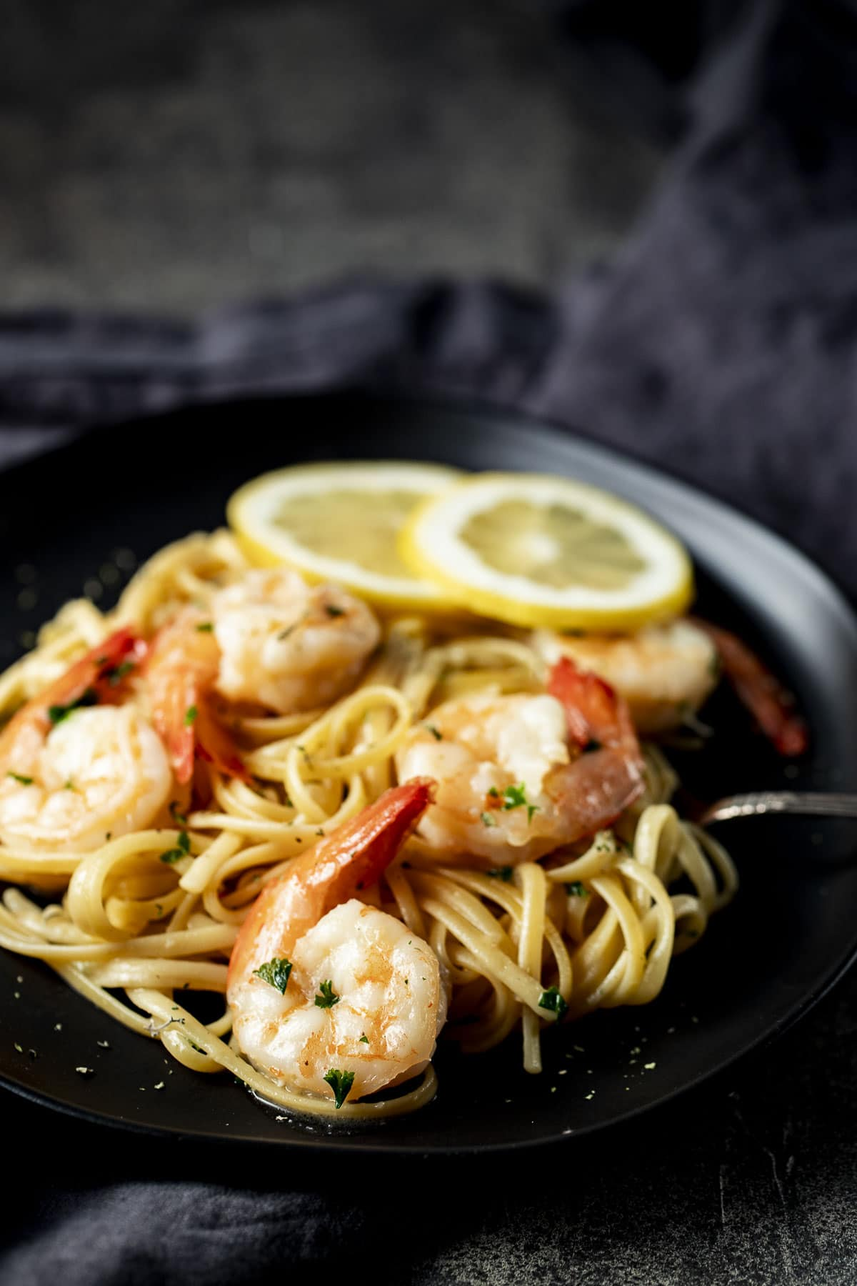 Side view of shrimp scampi on a black plate.