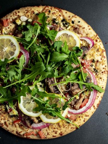 Overhead view of sardine pizza garnished with arugula and lemon slices.