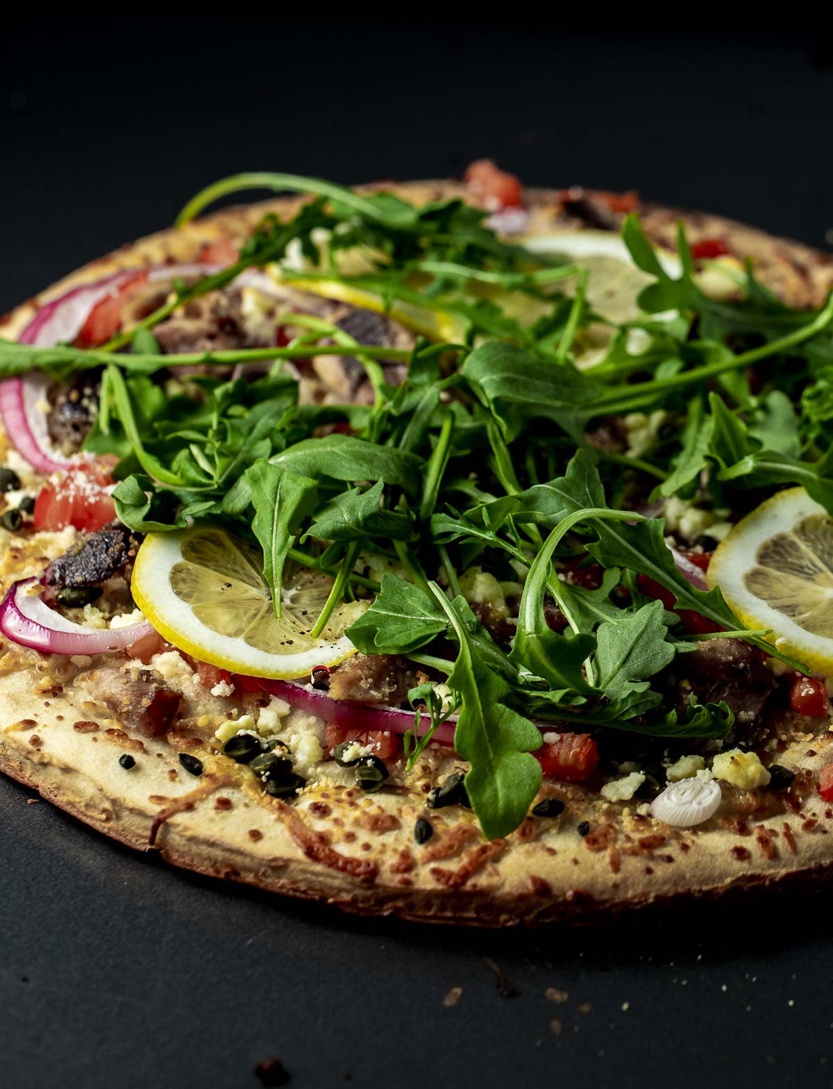 Side view of a whole sardine pizza topped with arugula.