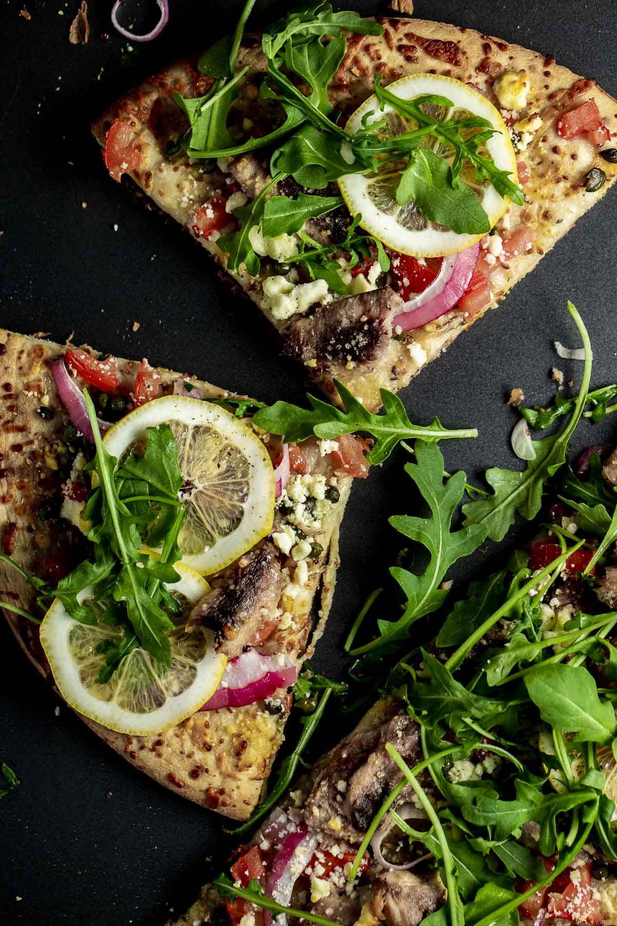 Overhead of slices of sardine pizza topped with lemon slices and arugula.
