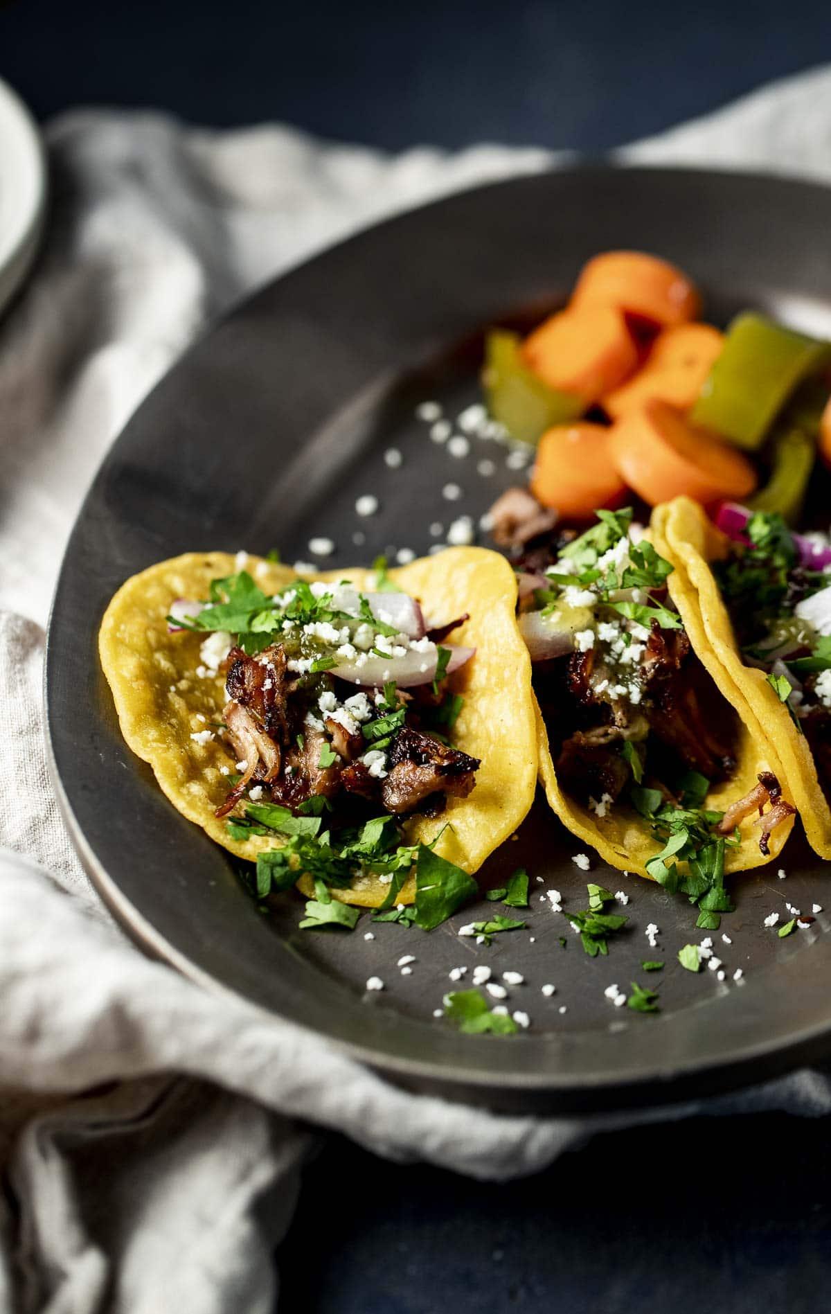 Pork carnitas tacos served on a black plate.