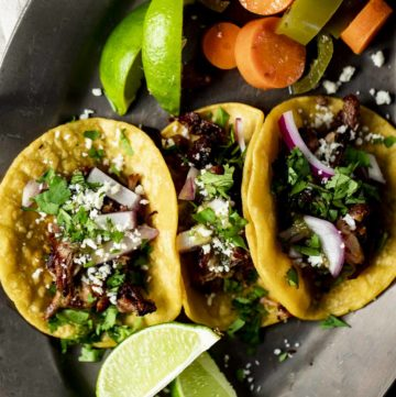 Overhead of pork carnitas served in corn tortillas with lemon wedges and pickled carrots and jalapeños on the side.