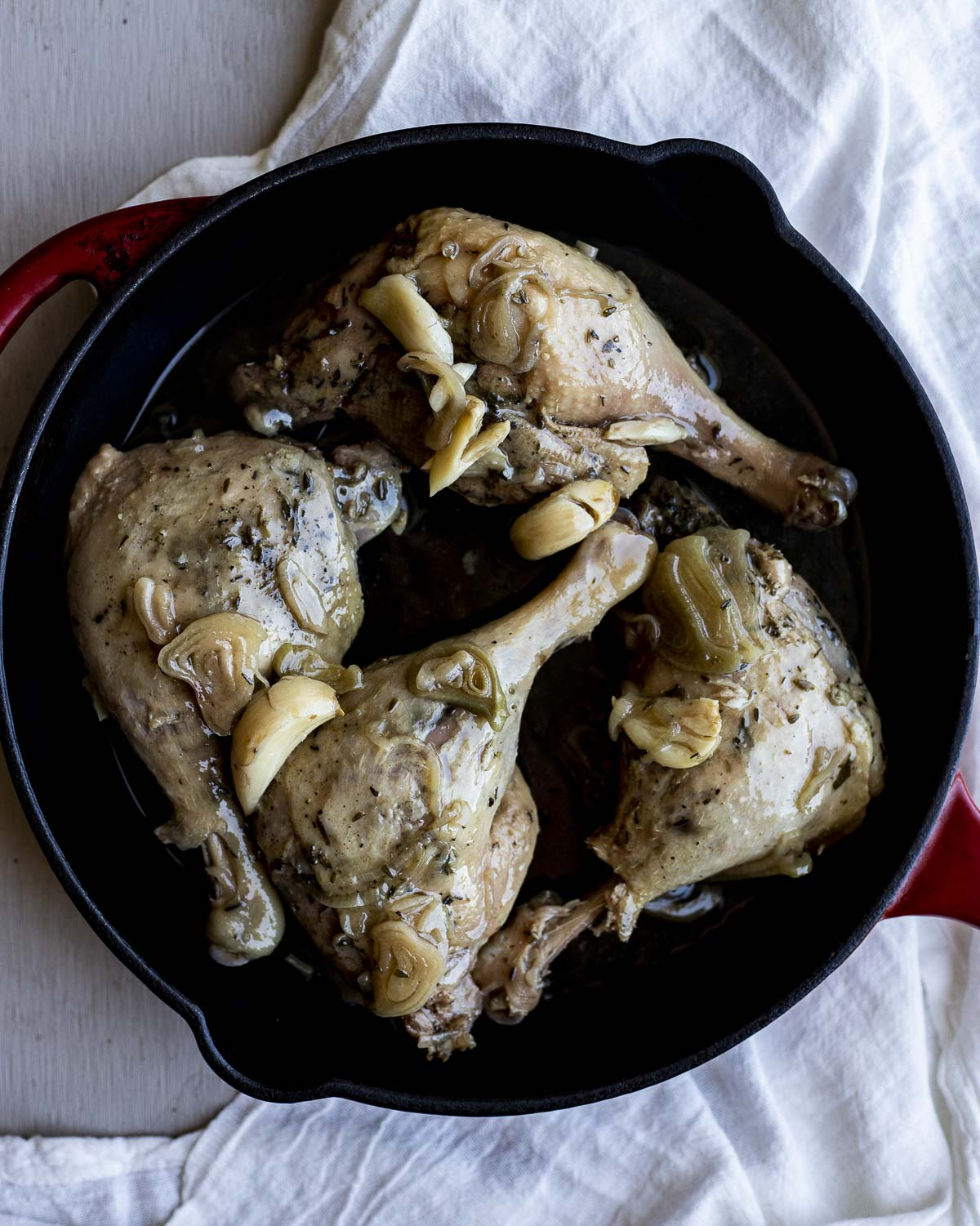 Four duck legs in a cast iron pan and ready to be broiled.
