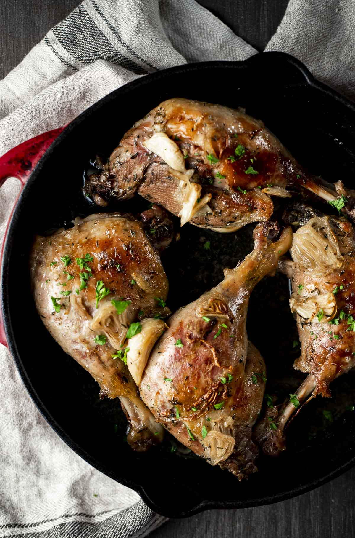 Four duck legs broiled in a cast iron pan.