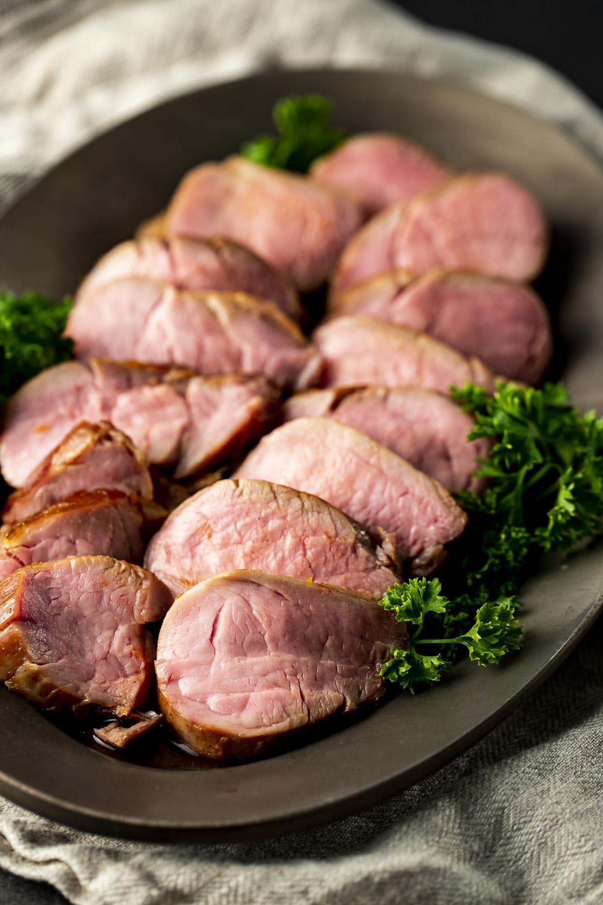 Slices of pork tenderloin arranged on a platter.