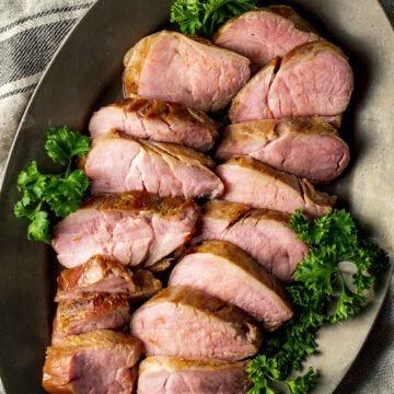 Pork tenderloin slices arranged on a platter with a herb garnish.