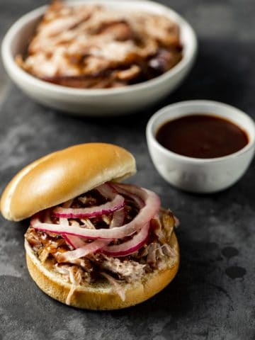 Pickled onions on top of pulled pork on a bun with BBQ sauce and pork in the background.