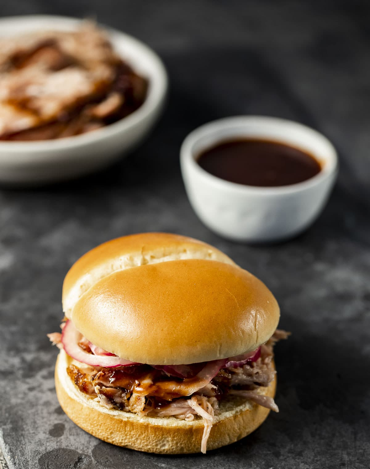 Pulled pork on a bun with BBQ sauce and pulled pork in the background.