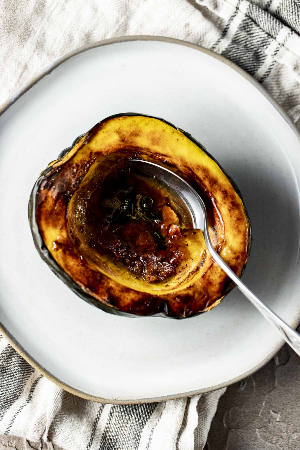 Overhead view of an air fried acorn squash half on a white plate with a spoon inserted into it.
