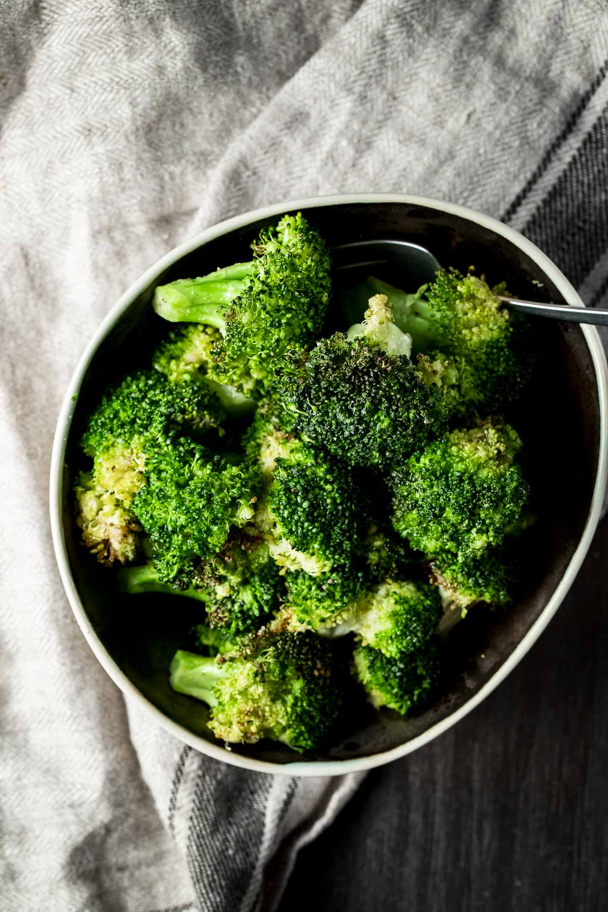 Overhead of air fried broccoli in a bowl.