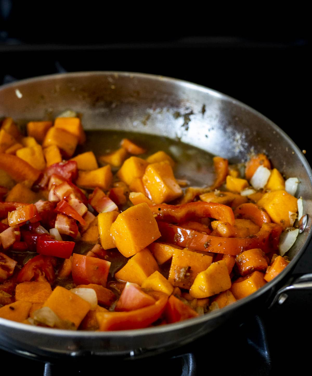 Chicken stock added to the pumpkin curry in the skillet.