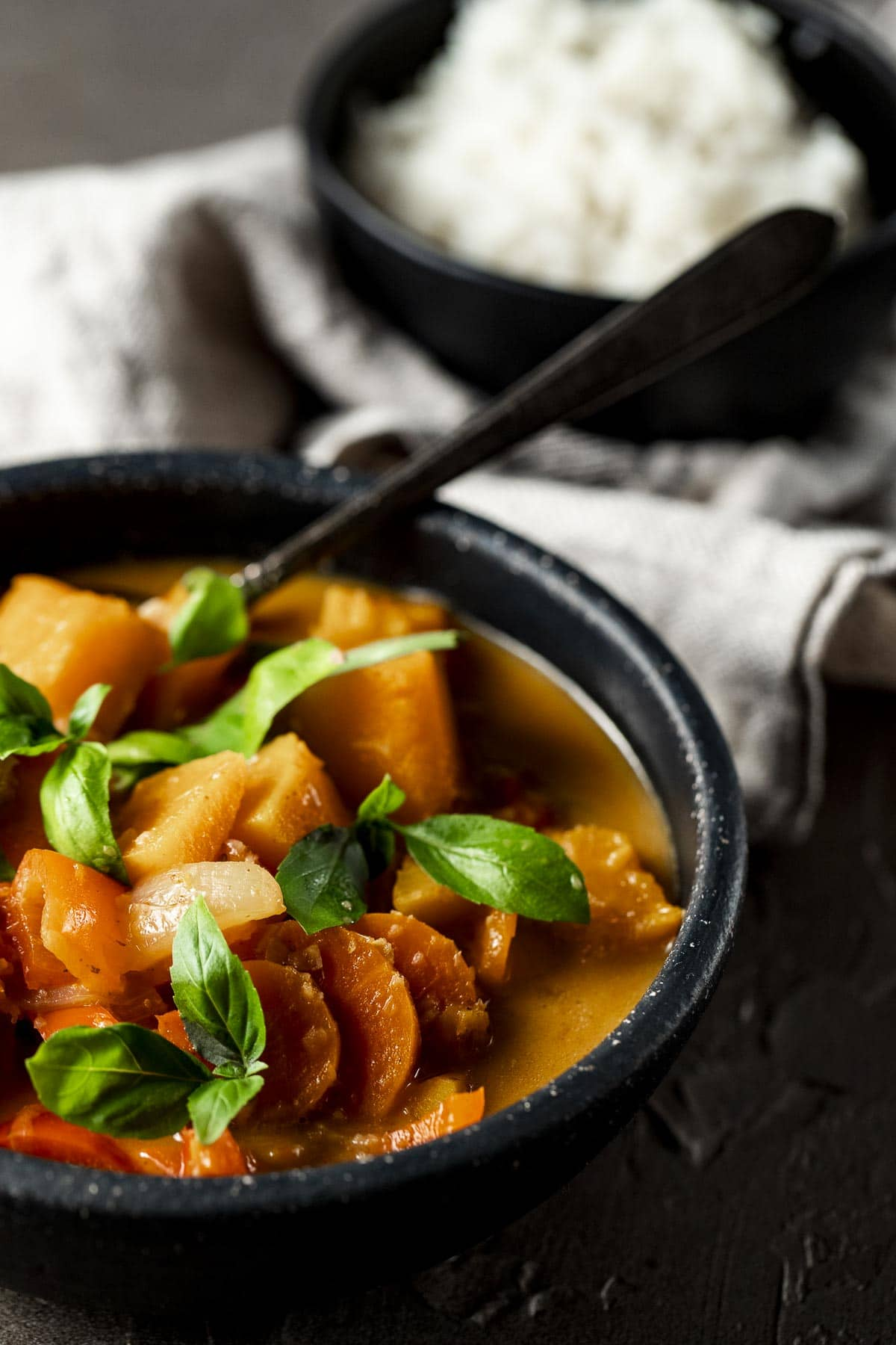 Side view of pumpkin curry in a bowl with a spoon.