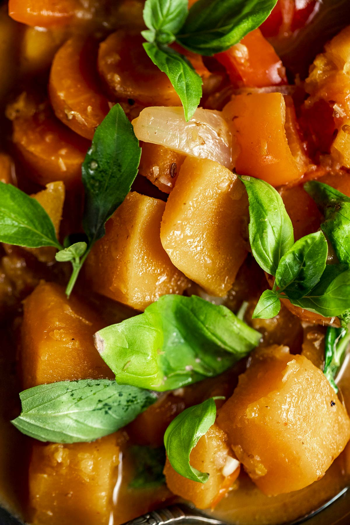 Close up of pumpkin curry topped with fresh basil leaves.