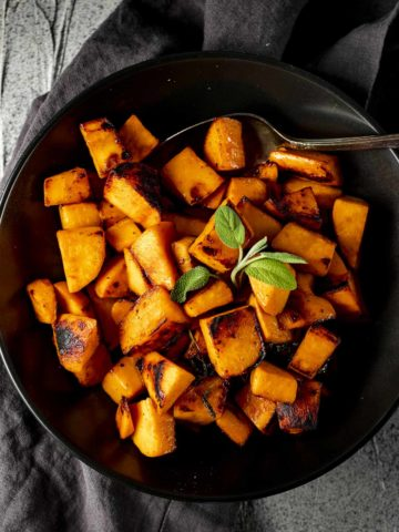 Overhead of sweet potato cubes served in a black bowl.